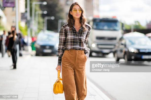 Felicia Akerstrom Ma wearing checked button shirt corduroy pants is seen during Stockholm Runway SS19 on August 28 2018 in Stockholm Sweden