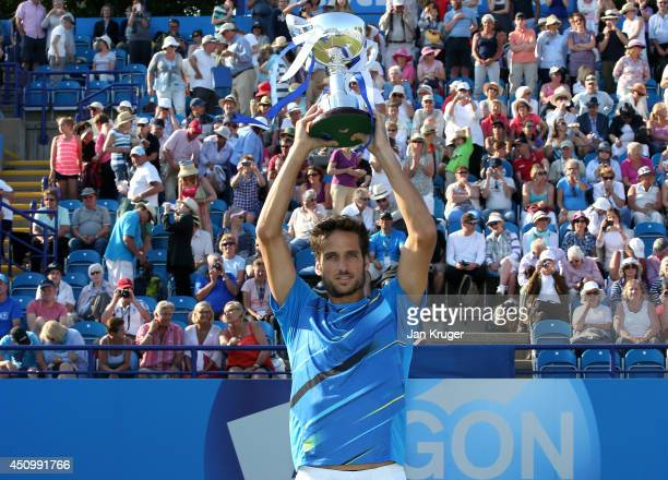 Feliciano Lopez of Spain celebrates with the trophy after beating Richard Gasquet of France during their Men's Singles Finals match on day eight of...