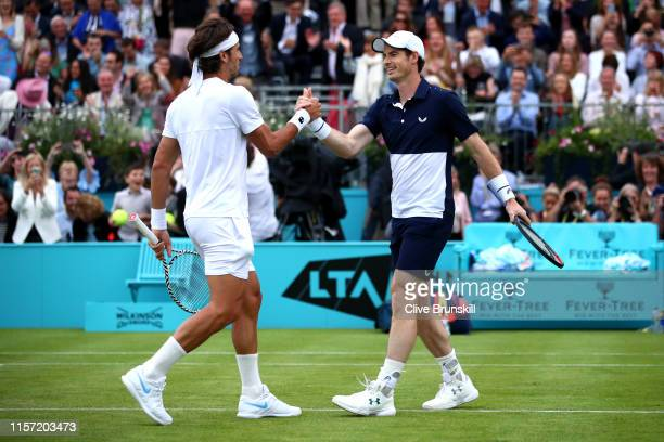 Feliciano Lopez of Spain embraces playing partner Andy Murray of Great Britain after winning their First Round Doubles match against Juan Sebastian...