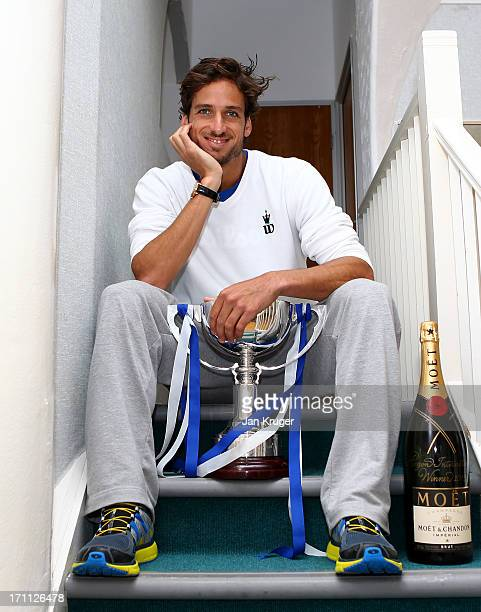Feliciano Lopez of Spain poses with the trophy after defeating Gilles Simon of France during his men's singles final match on day eight of the AEGON...