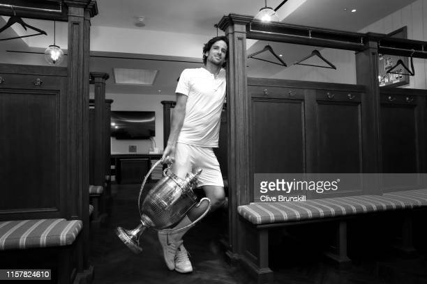 Feliciano Lopez of Spain poses with the winners trophies from the mens singles final and mens doubles final in the locker room during day seven of...