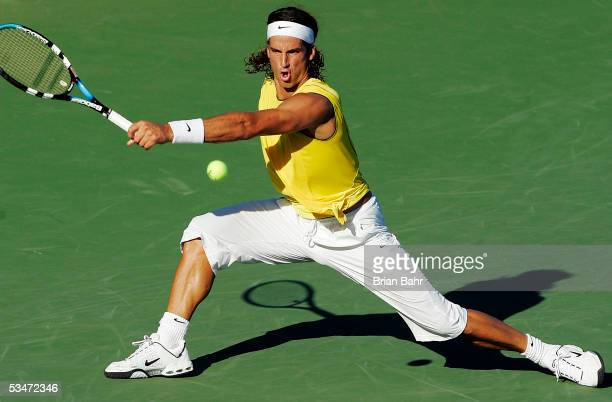 Feliciano Lopez of Spain slides to reach a volley from David Ferrer of Spain during the men's semifinals of the Pilot Pen Tennis tournament on August...