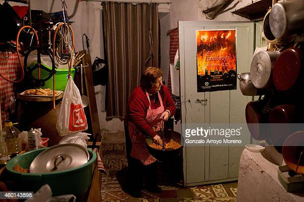 Felicita aged 76 carries a saucepan of 'Migas' from her kitchen for a group of revelers during the cella's route as part of the 'Los Escobazos'...