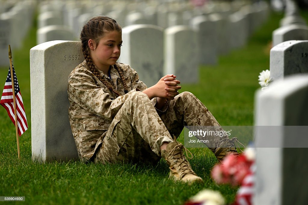 Felicity Bohn 11 of Littleton visits the grave of Gregory P. Rund USMC. He was a close high school friend of her mother Lauren where they were survivors of the Columbine shooting's. Lance Corporal Rund died Dec. 11 2004 as result of enemy action in Al Anbar Province, Iraq.He was awarded the Bronze Star for heroic achievement in connection with combat operations against the enemy. Memorial Day ceremony, 84th Anniversary of Remembrance at Fort Logan National Cemetery. May 30, 2016 in Denver, CO.