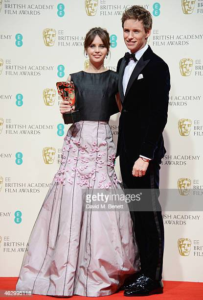 Felicity Jones and Eddie Redmayne pose with the Outstanding British Film award for The Theory of Everything in the winners room at the EE British...