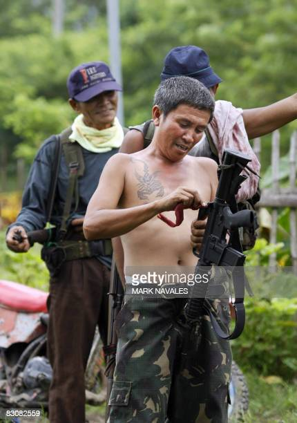 GUTIERREZ Felimon Cayang known as Commander Max and leader of the armed fanatical Ilaga Christian militiamen checks his firearm as they gather in...