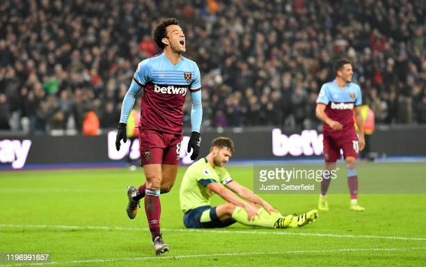 Felipe Anderson of West Ham United celebrates after scoring his team's fourth goal as Simon Francis of AFC Bournemouth reacts during the Premier...