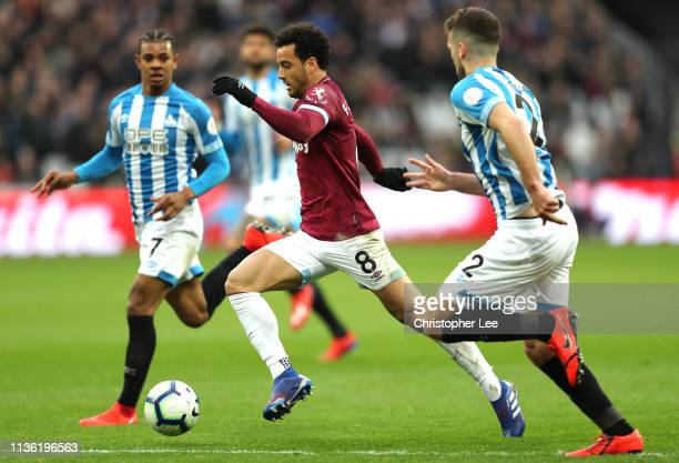 Felipe Anderson of West Ham United runs with the ball past Tommy Smith and Juninho Bacuna of Huddersfield Town during the Premier League match...