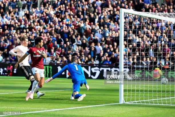 Felipe Anderson of West Ham United scores the opening goal pass David De Gea of Manchester United during the Premier League match between West Ham...