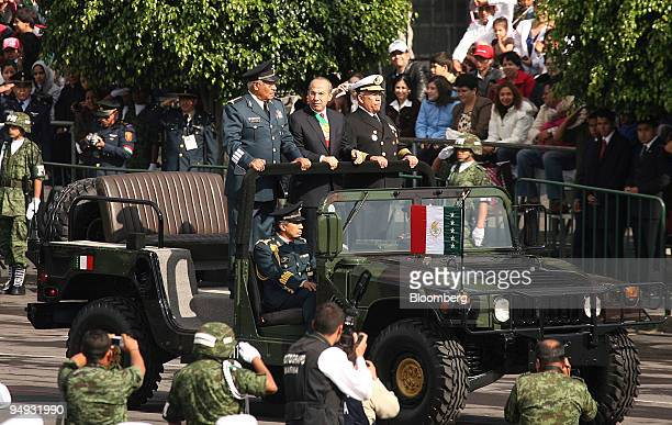 Felipe Calderon, Mexico's president, center, is flanked by Guillermo Galvan, defense minister, left, and Mariano Francisco, minister of the navy,...