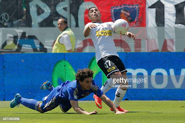 Felipe Flores of Colo Colo figths for the ball against Matias Corujo of Universidad De Chile during a match between Colo Colo and U de Chile as part...