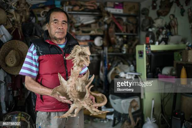 Felipe Linares son of Alebrijes creator Pedro Linares stands for a photograph with an unfinished alebrije Mexican folk art sculpture at his studio in...