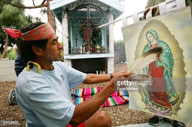 Felipe Martinez uses an eagle feather to fan copal smoke at a banner with an image of the Virgin of Guadalupe the patron saint of Mexico during a...