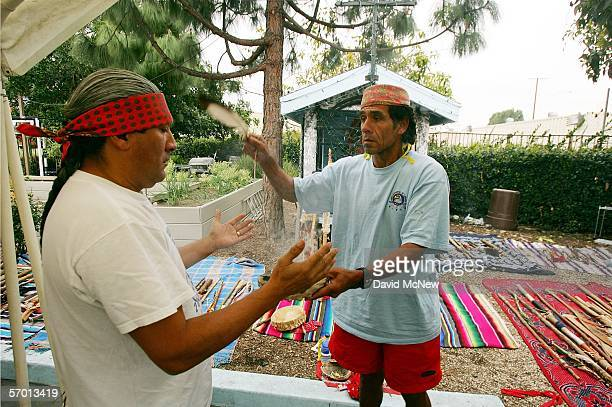 Felipe Martinez uses an eagle feather to fan copal smoke at fellow runner Al Gonzales in a Native American cleansing ceremonies for day laborers who...