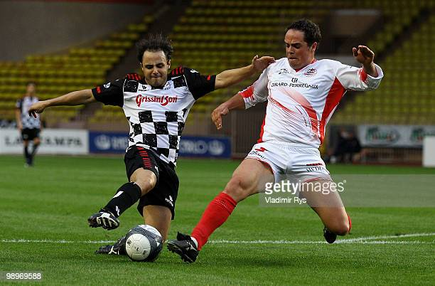 Felipe Massa of Brazil and Ferrari and Peter Fill battle for the ball during the football charity match between the Monaco star team and the team of...