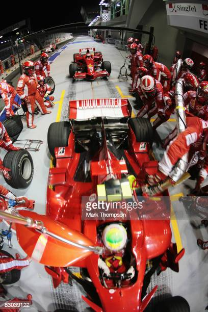 Felipe Massa of Brazil and Ferrari drives off with his refuelling hose still attached while Kimi Raikkonen of Finland and Ferrari waits behind to...