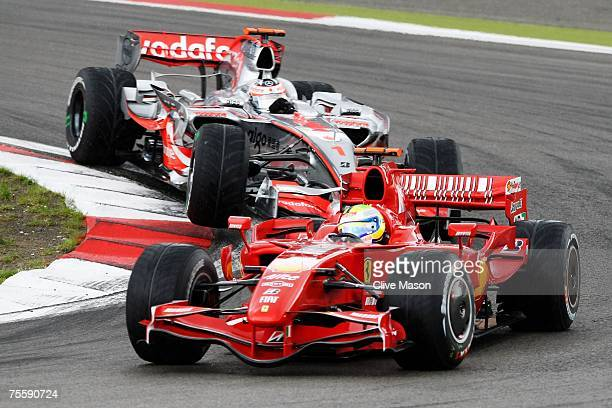 Felipe Massa of Brazil and Ferrari leads on the first corner from Fernando Alonso of Spain and McLaren Mercedes during the European Grand Prix at...