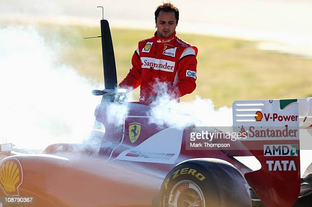 Felipe Massa of Brazil and Ferrari looks at his car following an engine problem during day three of winter testing at the Ricardo Tormo Circuit on...