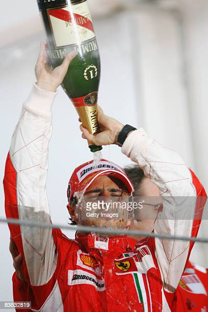 Felipe Massa of Brazil and Ferrari looks disappointed as he celebrates on the podium after winning the race but losing the World Championship at the...