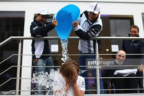 Felipe Massa of Brazil and Williams and Valtteri Bottas of Finland and Williams pour ice water over Williams deputy team principal Claire Williams in...