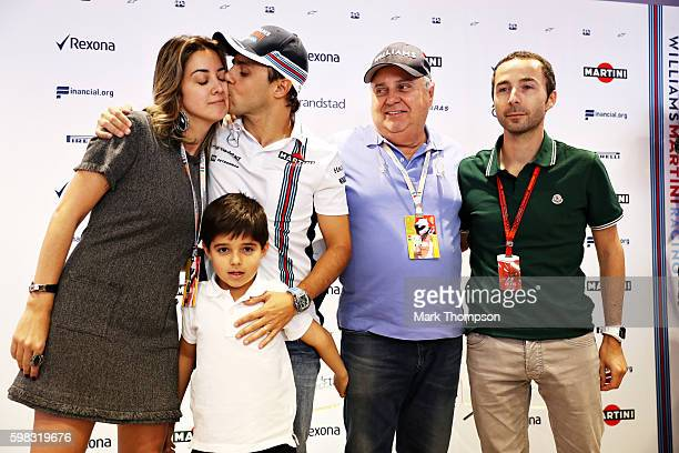 Felipe Massa of Brazil and Williams kisses his wife Anna Raffaela Bassi and stands with his son Felipinho Massa father Luís Antonio Massa and manager...