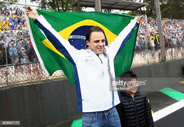 Felipe Massa of Brazil and Williams stands with a Brazilian flag for his last home Grand Prix with his son Felipinho on the drivers parade before the...