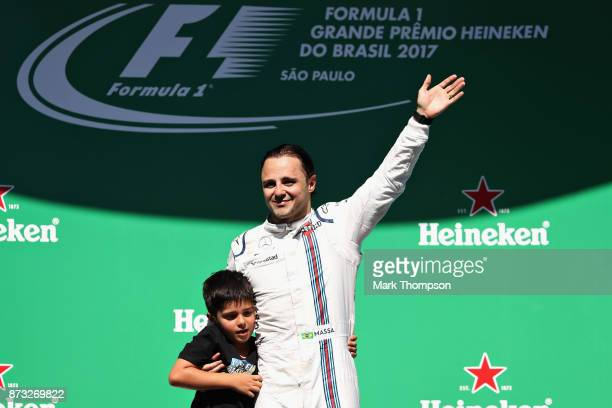 Felipe Massa of Brazil and Williams waves to the crowd with son Felipinho at his final Formula One Grand Prix of Brazil at Autodromo Jose Carlos Pace...