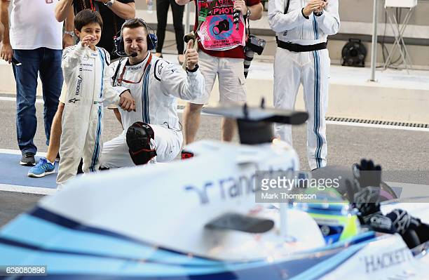 Felipe Massa of Brazil driving the Williams Martini Racing Williams FW38 Mercedes PU106C Hybrid turbo waves to his son Felipinho before his final F1...
