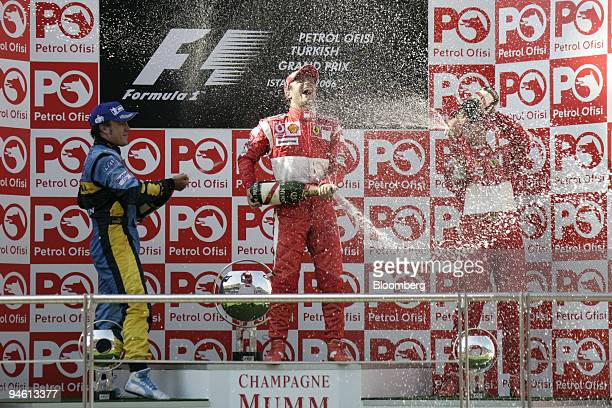 Felipe Massa of Team Ferrari center is sprayed by Fernando Alonso left and Michael Schumacher on the podium at the Formula 1 Grand Prix of Turkey in...