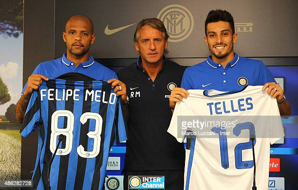 Felipe Melo and Alex Telles new signings for FC Internazionale Milano pose with the club shirt with FC Internazionale Milano coach Roberto Mancini...