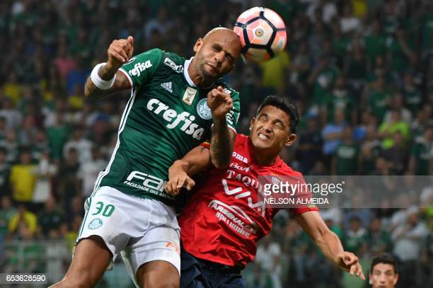 Felipe Melo of Brazil's Palmeiras jump for the ball with Jorge Ortiz of Bolivia's Jorge Wilstermann during their Libertadores Cup football match held...