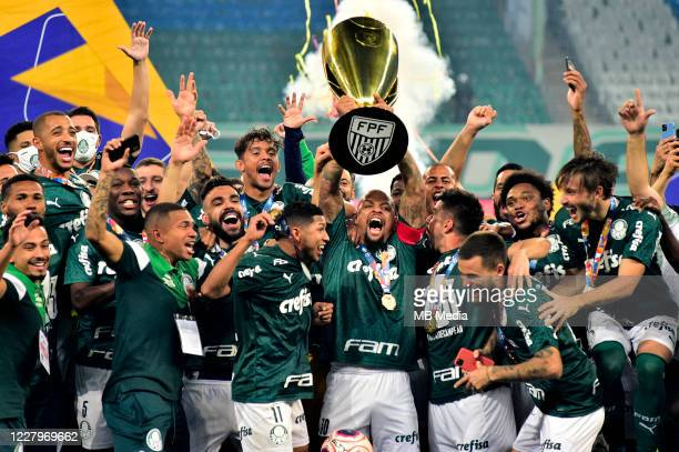 Felipe Melo of Palmeiras holds up the trophy with teammates as they celebrate winning the match between Palmeiras and Corinthians as part of the...