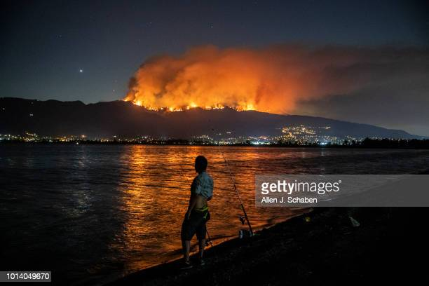 Felipe Montiel of San Marino fishes at Lake Elsinore as the Holy fire reflects across the water while burning in the Cleveland National Forest above...