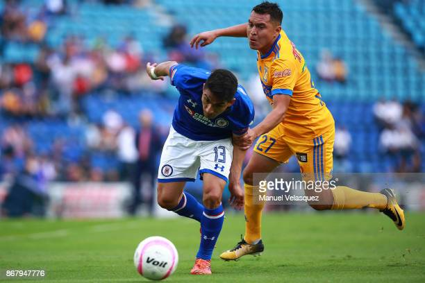 Felipe Mora of Cruz Azul passes the mark of Alberto Acosta of Tigres during the 15th round match between Cruz Azul and Tigres UANL as part of the...