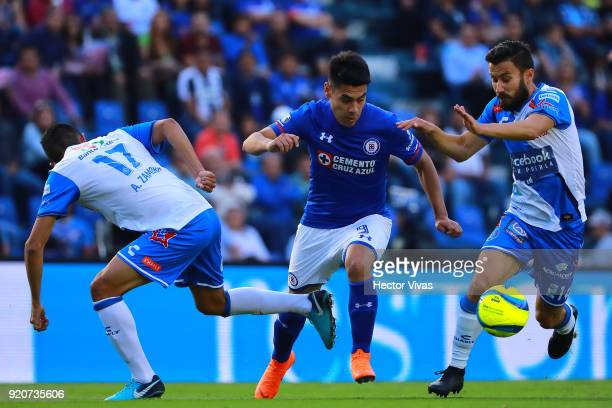 Felipe Mora of Cruz Azul struggles for the ball with Alonso Zamora and Jose Guerrero of Puebla during the 8th round match between Cruz Azul and...