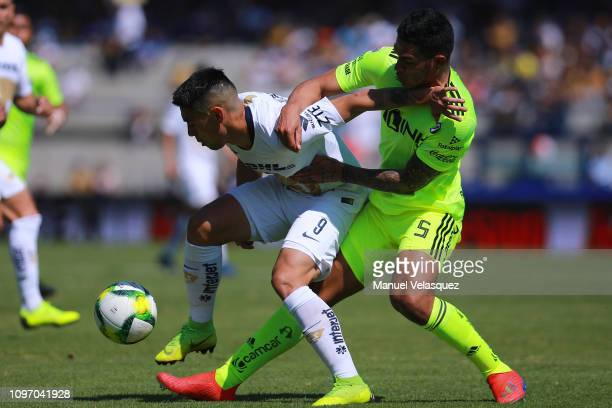 Felipe Mora of Pumas struggles for the ball against Anderson Santamaria of Atlas during the 3rd round match between Pumas UNAM and Atlas as part of...