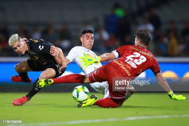 Felipe Mora of Pumas struggles for the ball with Gaspar Servio and Gustavo Canto of Dorados de Sinaloa during the quarterfinals match between Pumas...