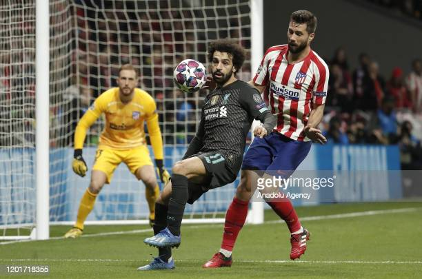Felipe of Atletico Madrid and Mohamed Salah of Liverpool vie for the ball during the UEFA Champions League round of 16 first leg soccer match between...