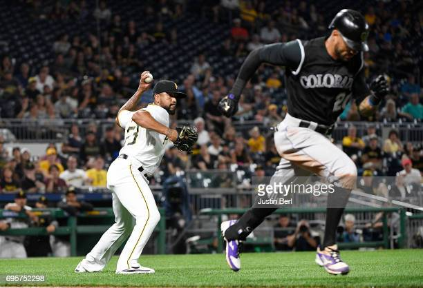 Felipe Rivero of the Pittsburgh Pirates throws to first base for a force out of Ian Desmond of the Colorado Rockies in the ninth inning during the...