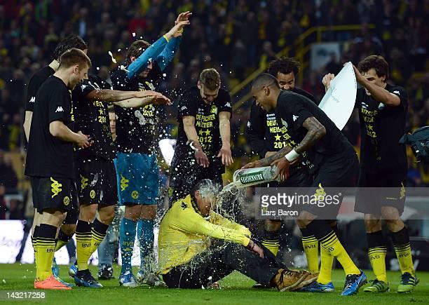 Felipe Santana of Dortmund and his team mates give Norbert Dickel a beer shower after the Bundesliga match between Borussia Dortmund and Borussia...