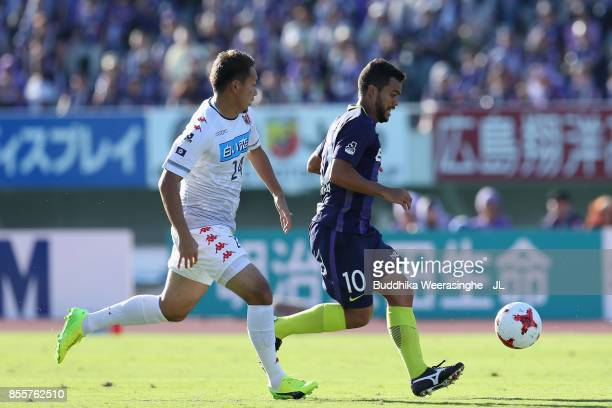 Felipe Silva of Sanfrecce Hiroshima controls the ball under pressure of Akito Fukumori of Consadole Sapporo during the JLeague J1 match between...