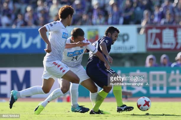 Felipe Silva of Sanfrecce Hiroshima controls the ball under pressure of Akito Fukumori and Hiroki Miyazawa of Consadole Sapporo during the JLeague J1...