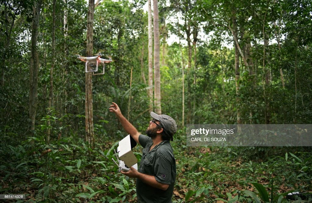 Felipe Spina Avino, World Wildlife Fund (WWF) forestry conservation analyst uses a drone to map an area of rainforest in the Ituxi reserve in the Western Amazon region of Brazil on September 18, 2017. Parts of the Western Amazon rainforest have suffered some of the heaviest deforestion in the Amazon as a whole, with figures puting it at a third higher than last year. Illegal logging has been hard to police in a country in economic crisis. / AFP PHOTO / CARL DE SOUZA / TO GO WITH AFP STORY by PAULA