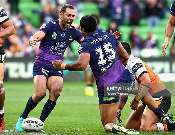 Felise Kaufusi of the Storm celebrates with teammate Cameron Smith of the Storm after crossing the line to score a try during the round 16 NRL match...