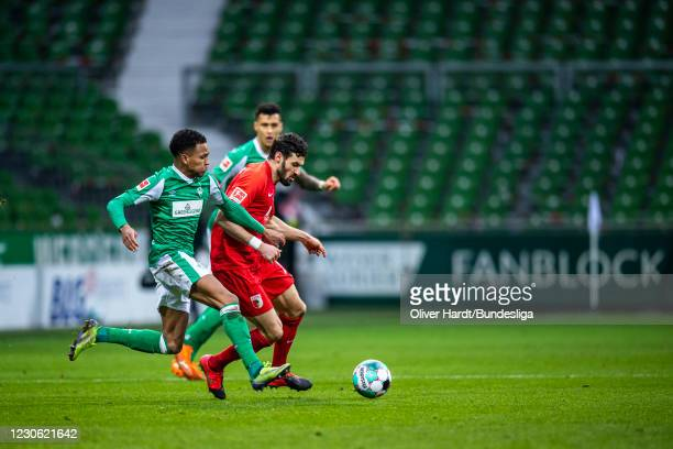 Felix Agu of SV Werder Bremen competes for the ball with Daniel Caligiuri of FC Augsburg during the Bundesliga match between SV Werder Bremen and FC...
