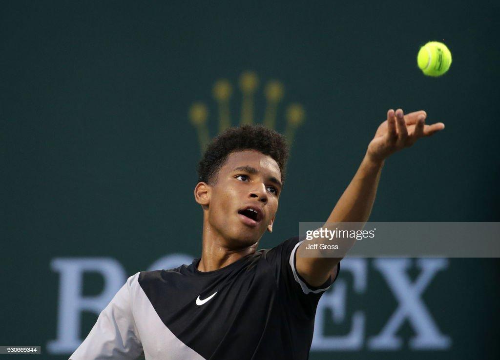 Felix Auger Aliassime of Canada tosses the ball up before serving to Milos Raonic of Canada during the BNP Paribas Open on March 11, 2018 at the Indian Wells Tennis Garden in Indian Wells, California.