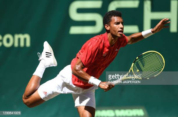 Felix Auger-Aliassime from Canada serves the ball to France's Ugo Humbert during their semi-final match at the ATP 500 Halle Open tennis tournament...