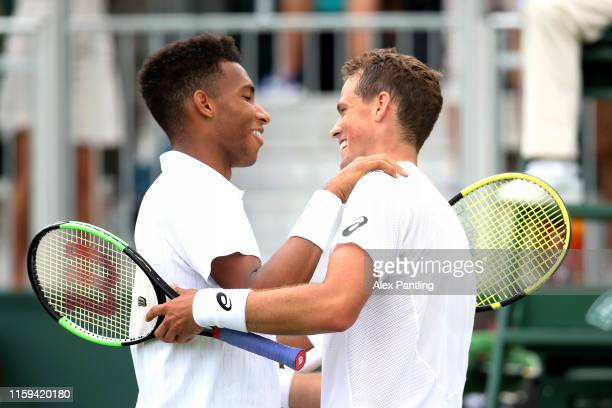 Felix AugerAliassime of Canada embraces Vasek Pospisil of Canada at the net after his Men's Singles first round match against Vasek Pospisil of...