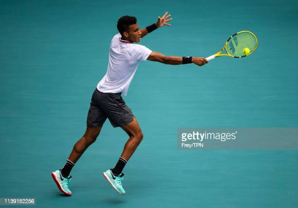 Felix AugerAliassime of Canada hits a backhand against John Isner of The United States in the semi final of the men's singles at the Miami Open at...