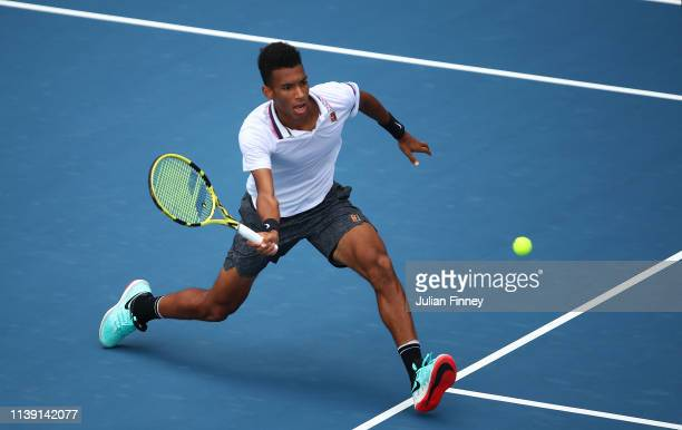 Felix AugerAliassime of Canada in action against John Isner of USA in the semi final during day twelve of the Miami Open tennis on March 29 2019 in...